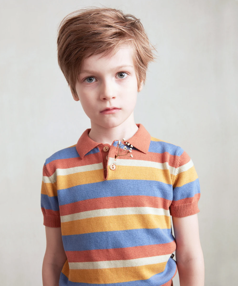 Boy looks into the camera wearing a knit striped polo in orange, cream, yellow, and cornflower blue. He has a small sprig of baby's breath tucked into his buttonhole.