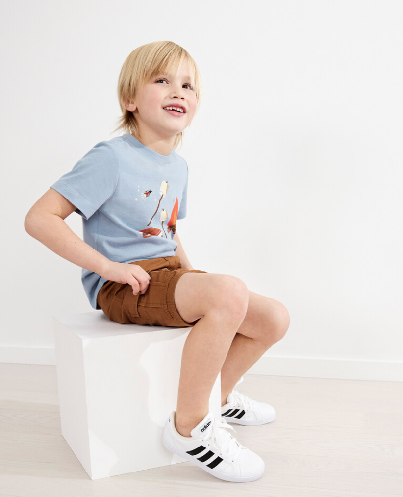 Boy wearing a blue tee and brown shorts sits on a white box and smiles