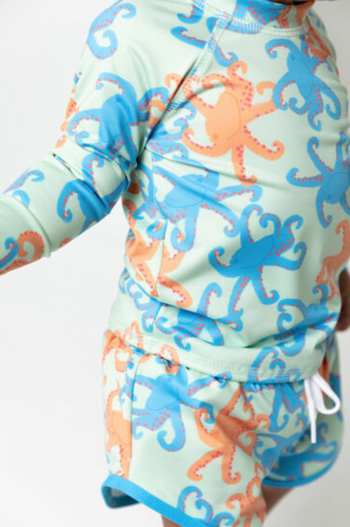 a matching rashguard and swim trunk set featuring range and blue octopuses on a mint green background.