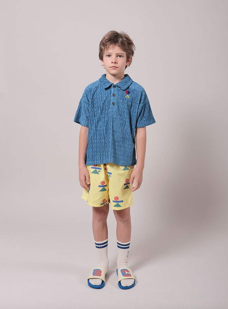 A boy in a blue polo shirt and yellow shorts with balancing shapes looks into the camera.