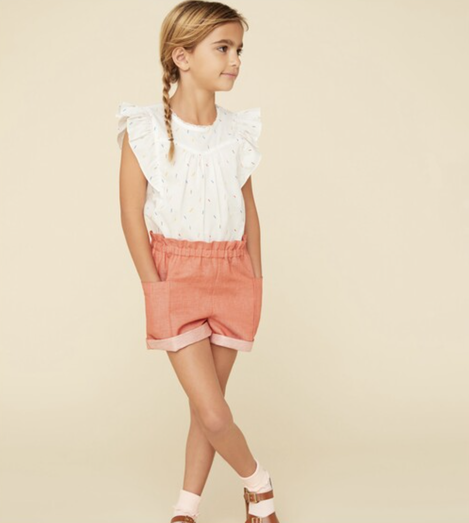 A girl wears a white ruffle sleeve blouse with multicolored sprinkles on it and salmon shorts