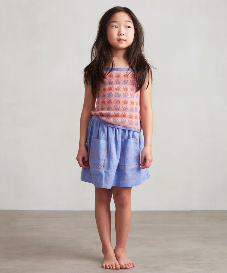 A girl wears a pink, orange, and blue jacquard tank top with a blue rick rack trimmed skirt