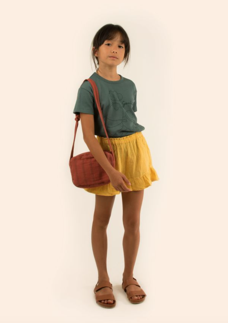 A girl wears a forest green shirt, mustard yellow frilled shorts, and sandals.