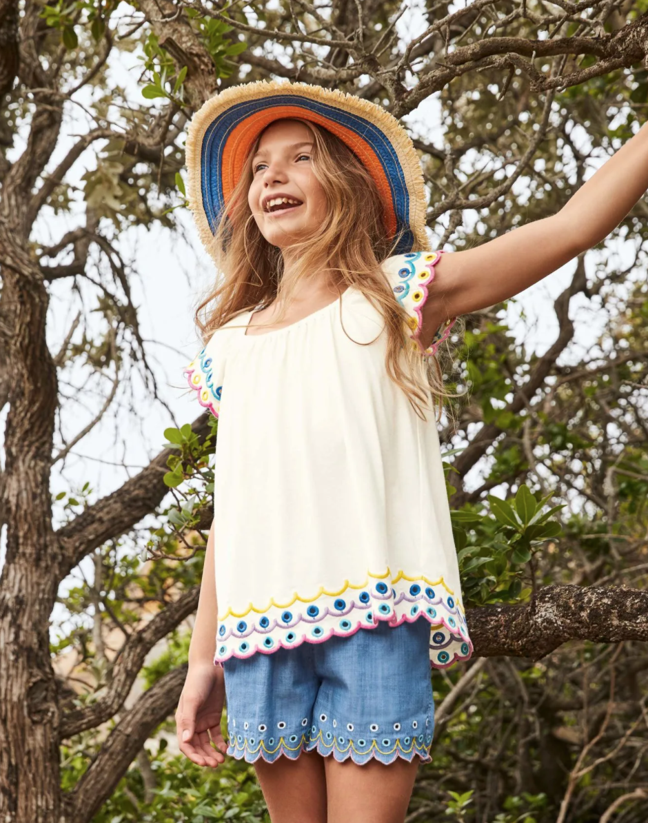 A girl wears a floppy sun hat, an embroidered blouse and chambray scalloped shorts