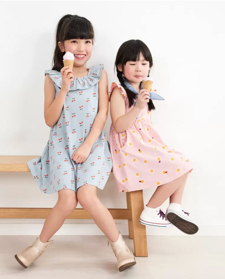 Two girls eat ice cream on a bench. The one on the left is wearing a blue ruffle neck dress with cherries printed on it.