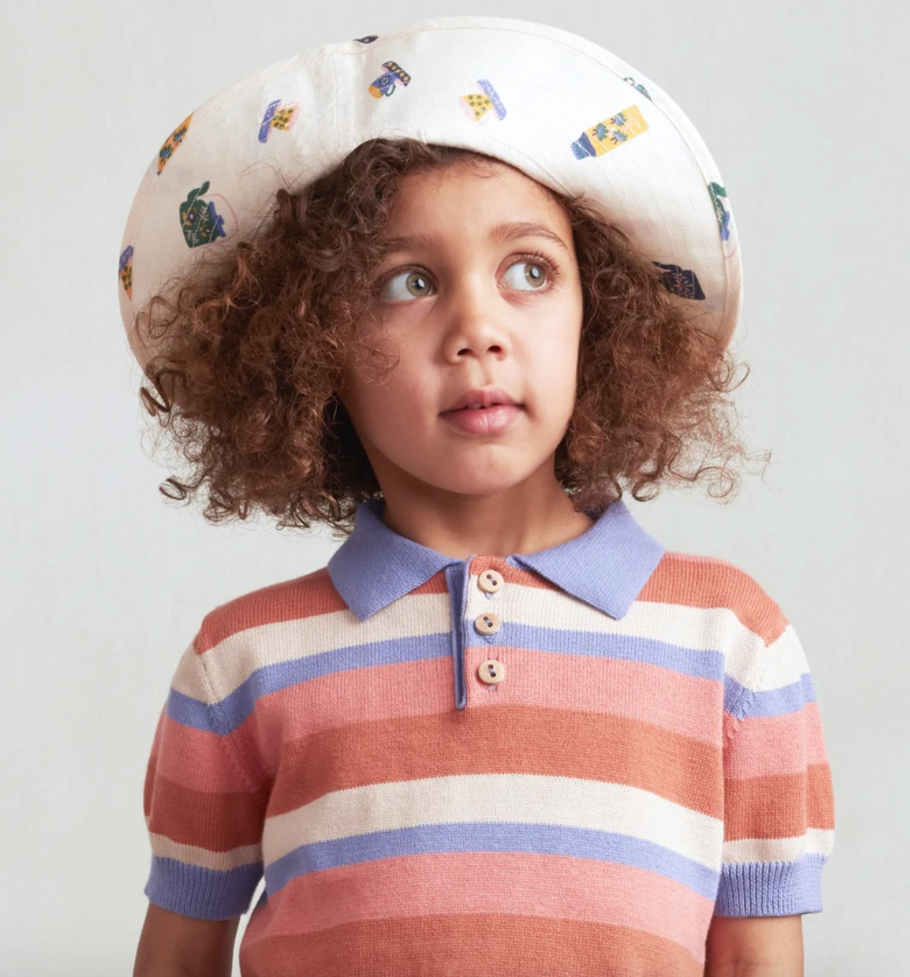 A girl wears a knitted button up shirt and a hat.