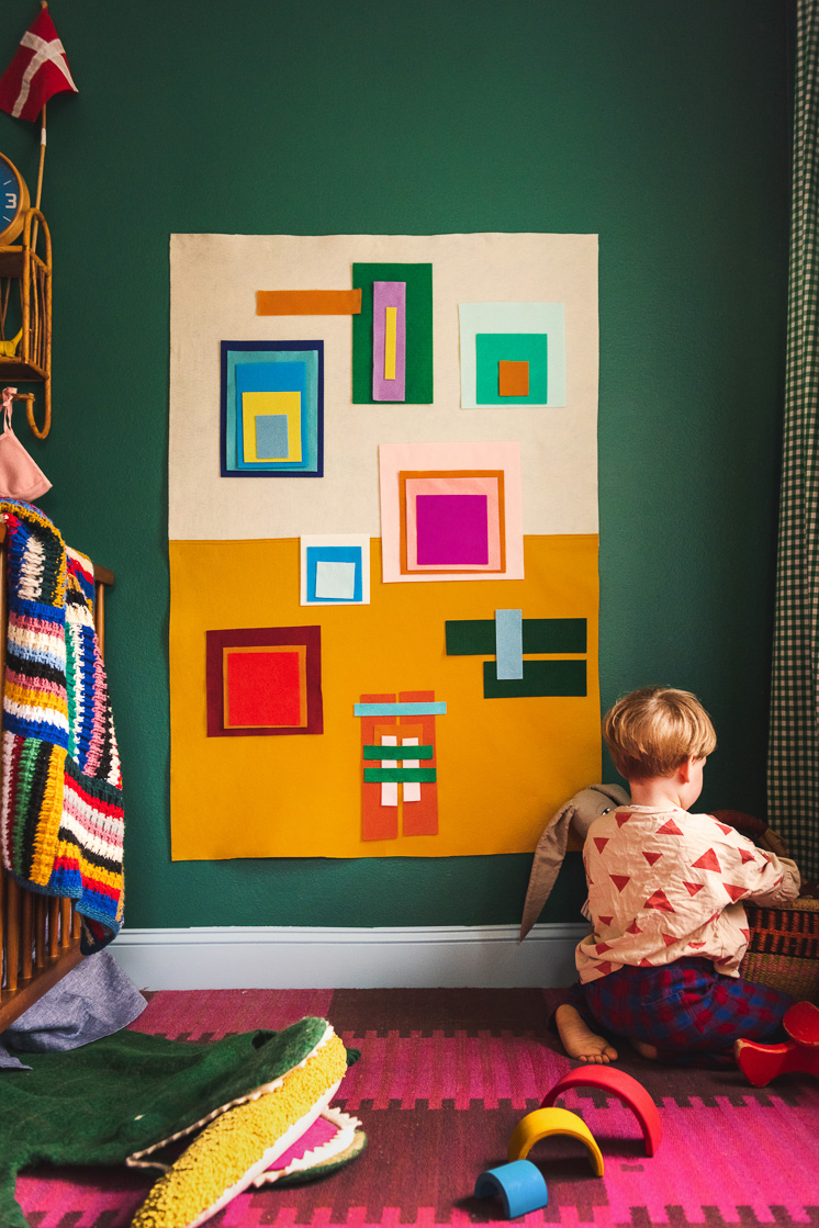 Jasper sits in front of a colorful Josef Albers-inspired felt board in a colorful room