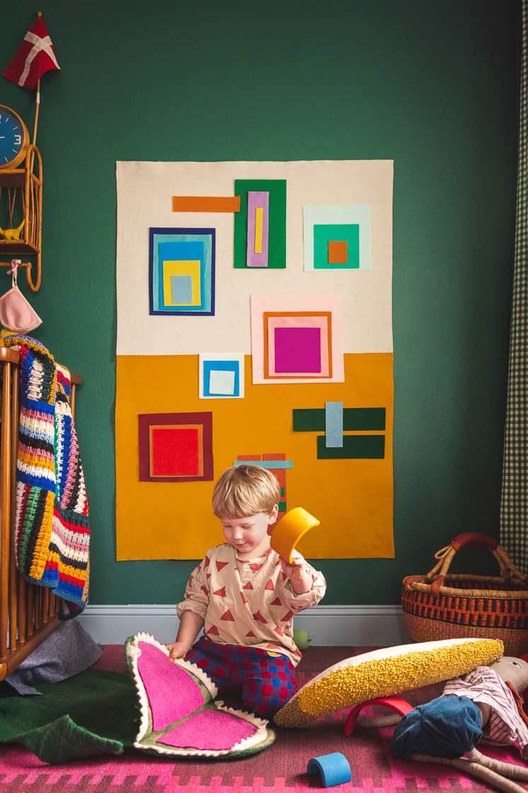 Jasper playing with an Albers-inspired felt board in a colorful room