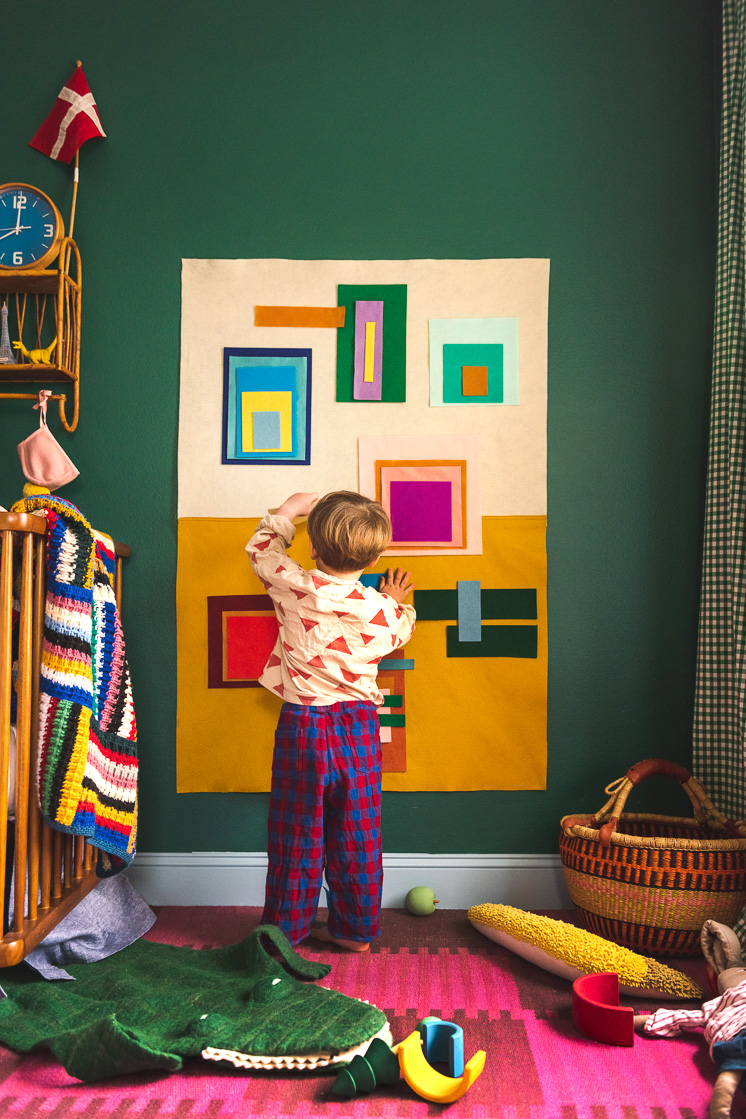 Jasper in a colorful room. He's playing with a colorful felt board made of bright squares and rectangles