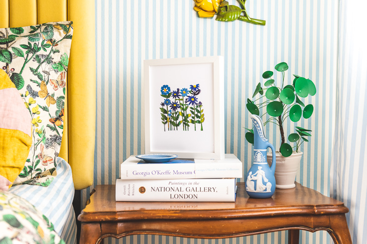Field of Colored Flowers Papercut print by Julie Marabelle on a stack of books in a blue striped bedroom