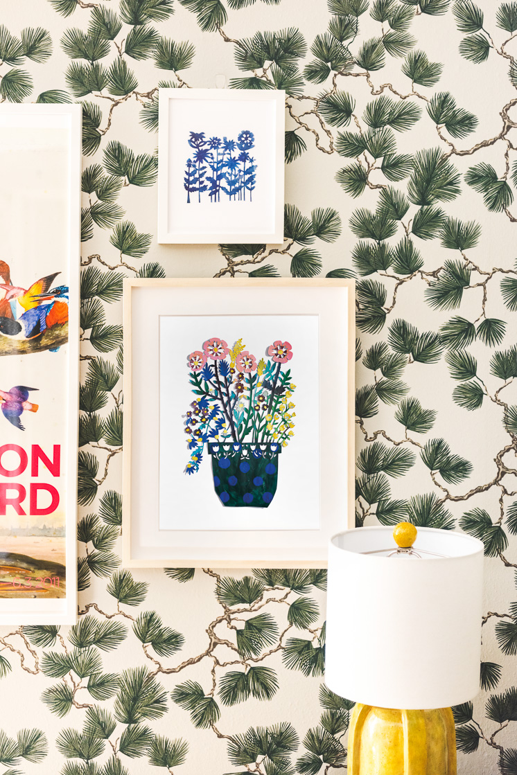 Field of Blue Flowers Papercut and Colored Potted Flowers Papercut art prints by Julie Marabelle on a wall with spruce-themed wallpaper.