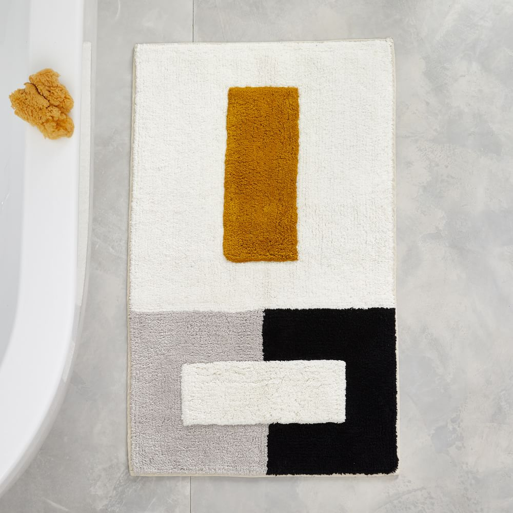 A grey, white, black, and gold colorblock bath mat
