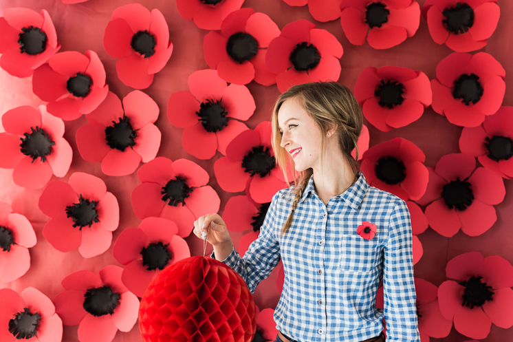 A woman holds a paper ornament in front of a wall of paper poppies