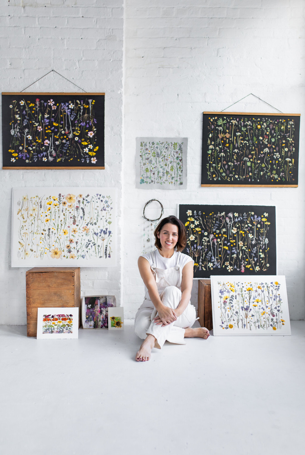 Tricia Paoluccio sits in a white room with lots of intricate botanical artworks on the walls and floor around her.