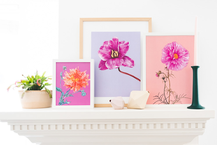 Three pink floral art prints on a white mantle next to a potted plant and a green candlestick