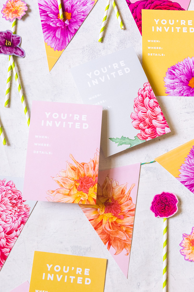 Floral party invitations with different flowers on pink, grey, and yellow backgrounds sit amongst floral bunting and cake toppers.