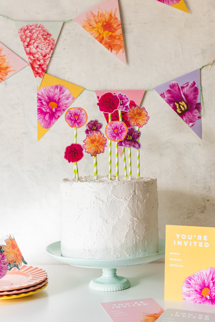 Sherbet-colored floral bunting hangs in the background. A white frosted cake with floral cake toppers sits on a mint green cake stand. Invitations and a floral crown peek in at the corners.