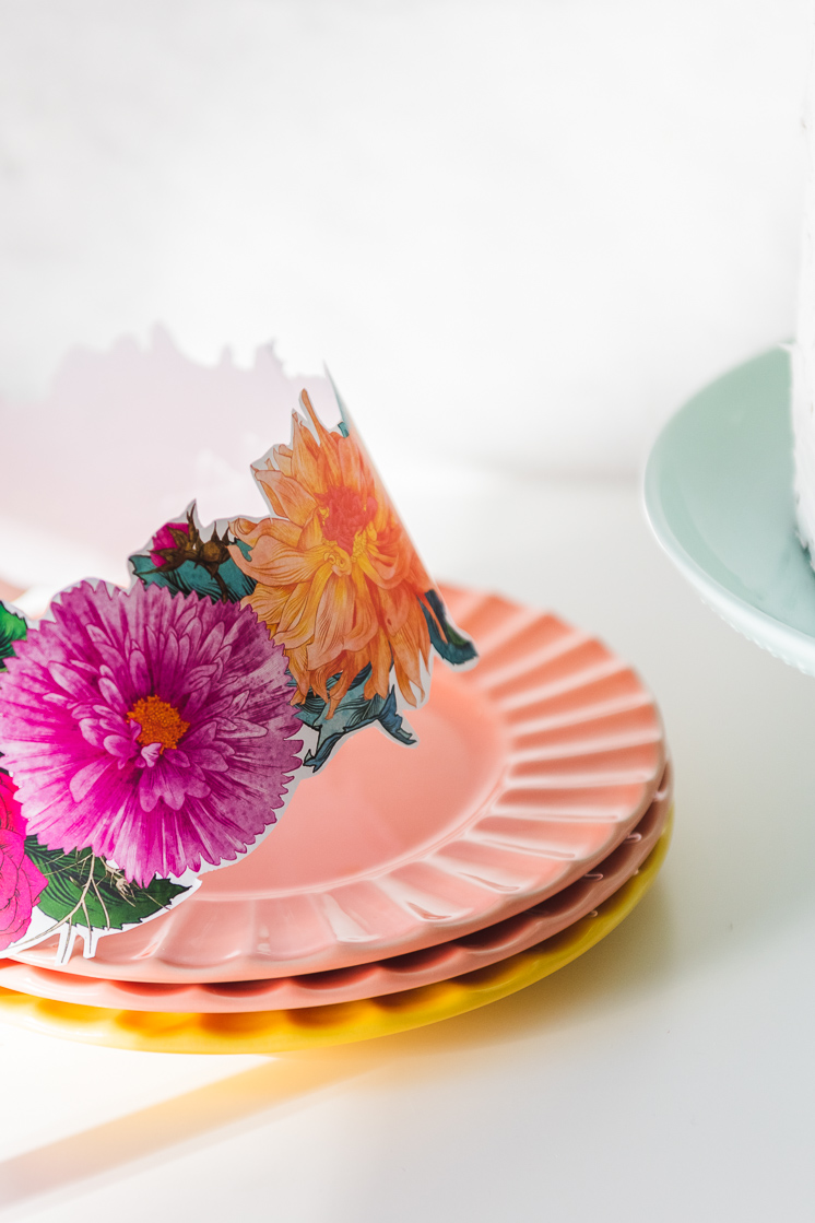 Detailed drawings of flowers make up a fuchsia and orange flower crown, which is resting on a pile of sherbet-colored plates.