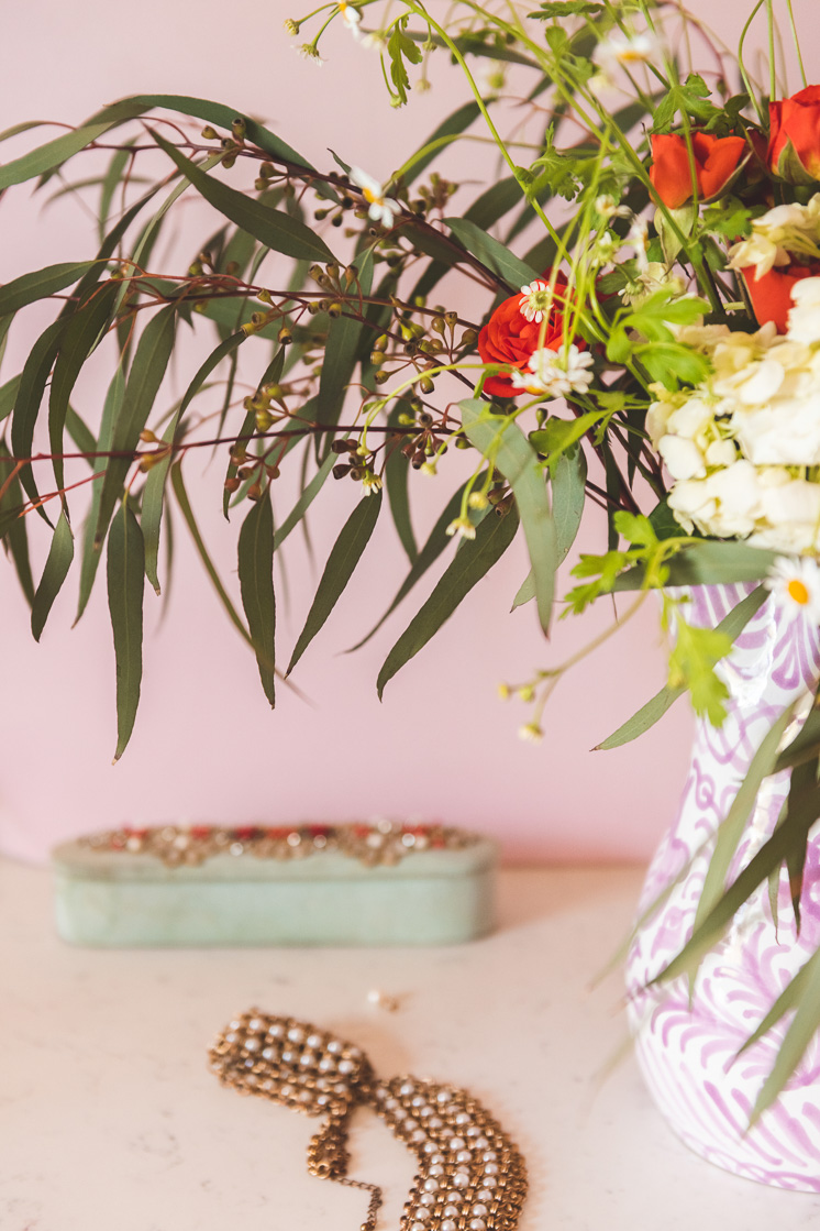 Detail shot of eucalyptus leaves, chamomile, roses, and hydrangeas against a pink wall with a mint green jewelry box in the background.