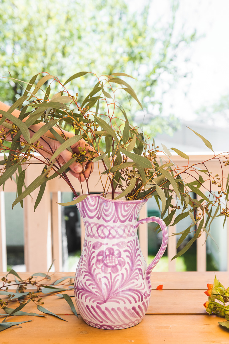 A person arranges eucalyptus branches in a purple and white vase.
