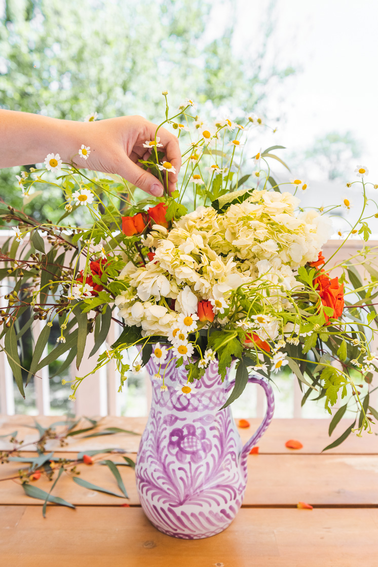 A person places chamomile blossoms in a bouquet of eucalyptus, roses, and hydrangeas in a purple and white vase.