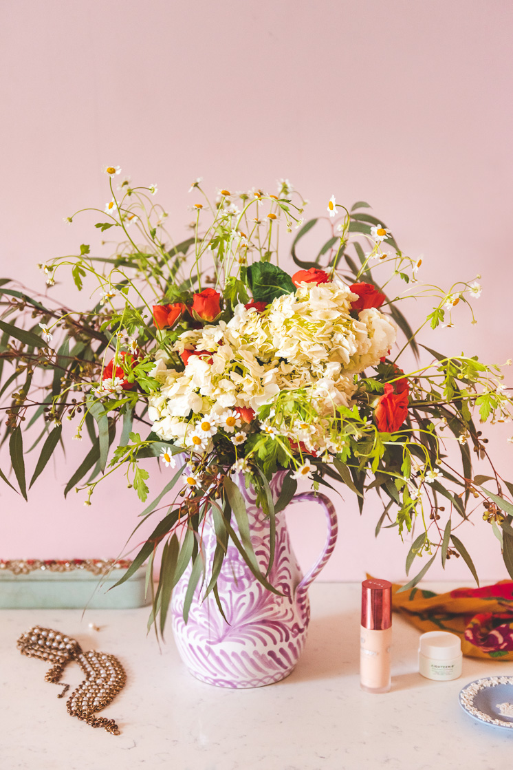 A bouquet made of eucalyptus leaves, chamomile, roses, and hydrangeas against a pink wall with a mint green jewelry box in the background.