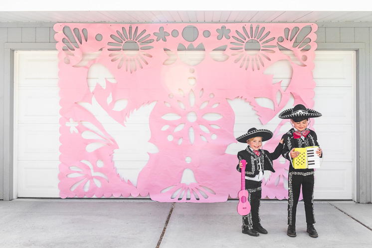 Two little boys dressed in Mariachi outfits holding cardboard instruments stand in front of a giant pink papel picado decoration