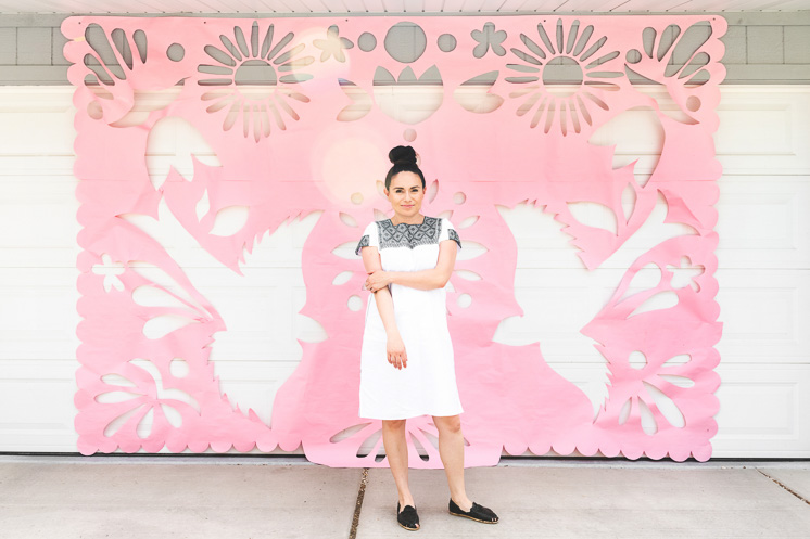 Nadia Aguilar Cates stands in front of a giant pink papel picado decoration