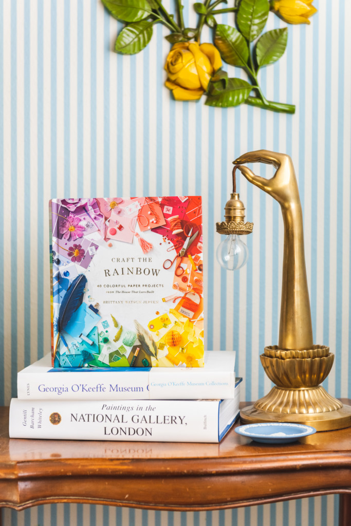 Craft the Rainbow book on a table with a brass hand-shaped lamp against a striped wall.