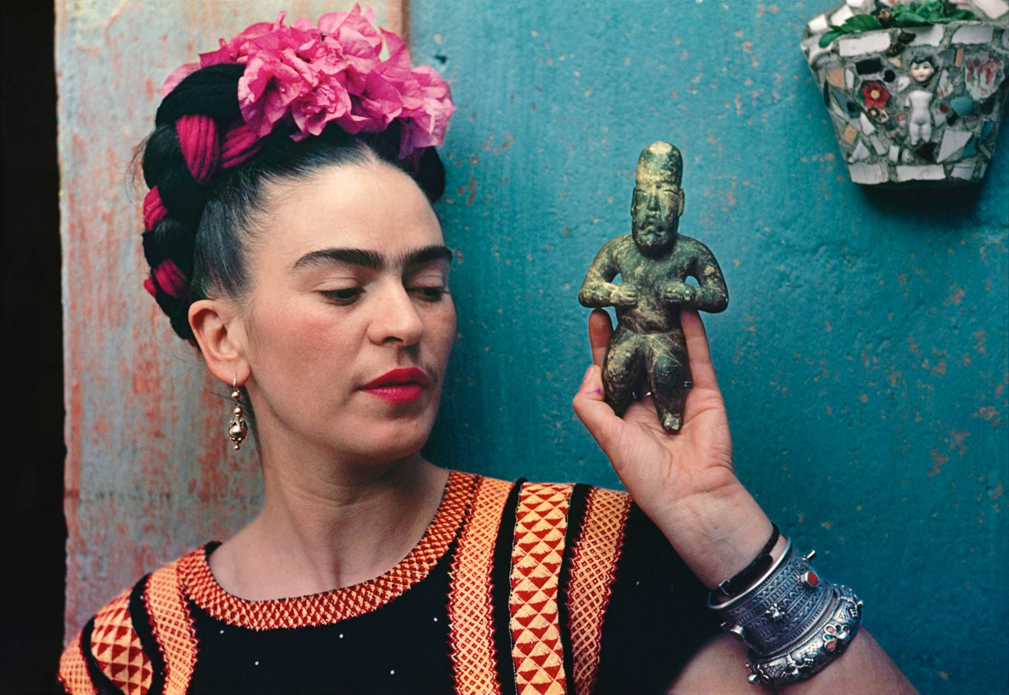 Photograph of Frida Kahlo holding a small carved idol. She's wearing a black and orange woven top and has flowers and ribbons braided into her hair, and she's standing against a turquoise wall.