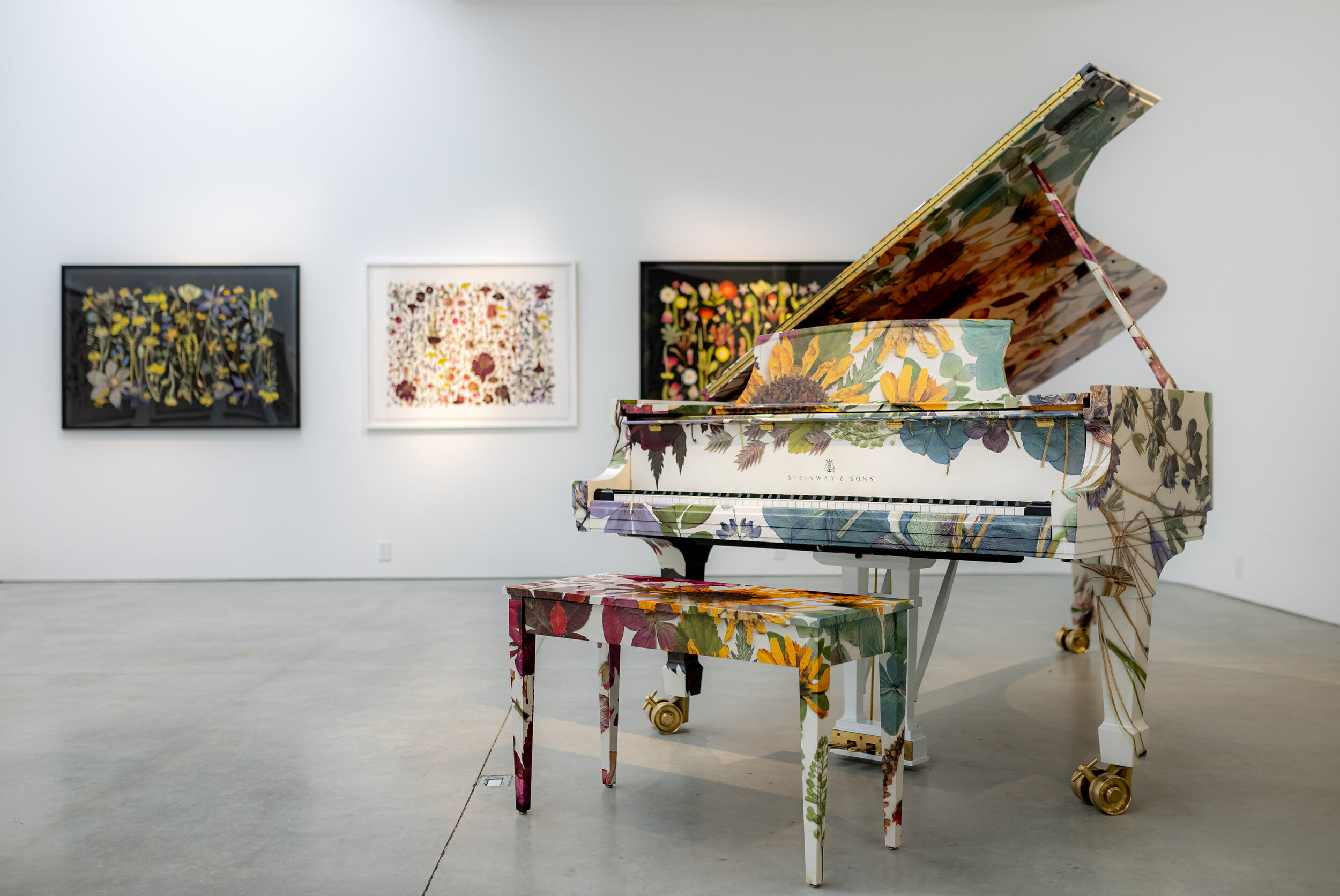 A botanically wrapped Steinway piano in a white gallery with botanical flower prints on the walls