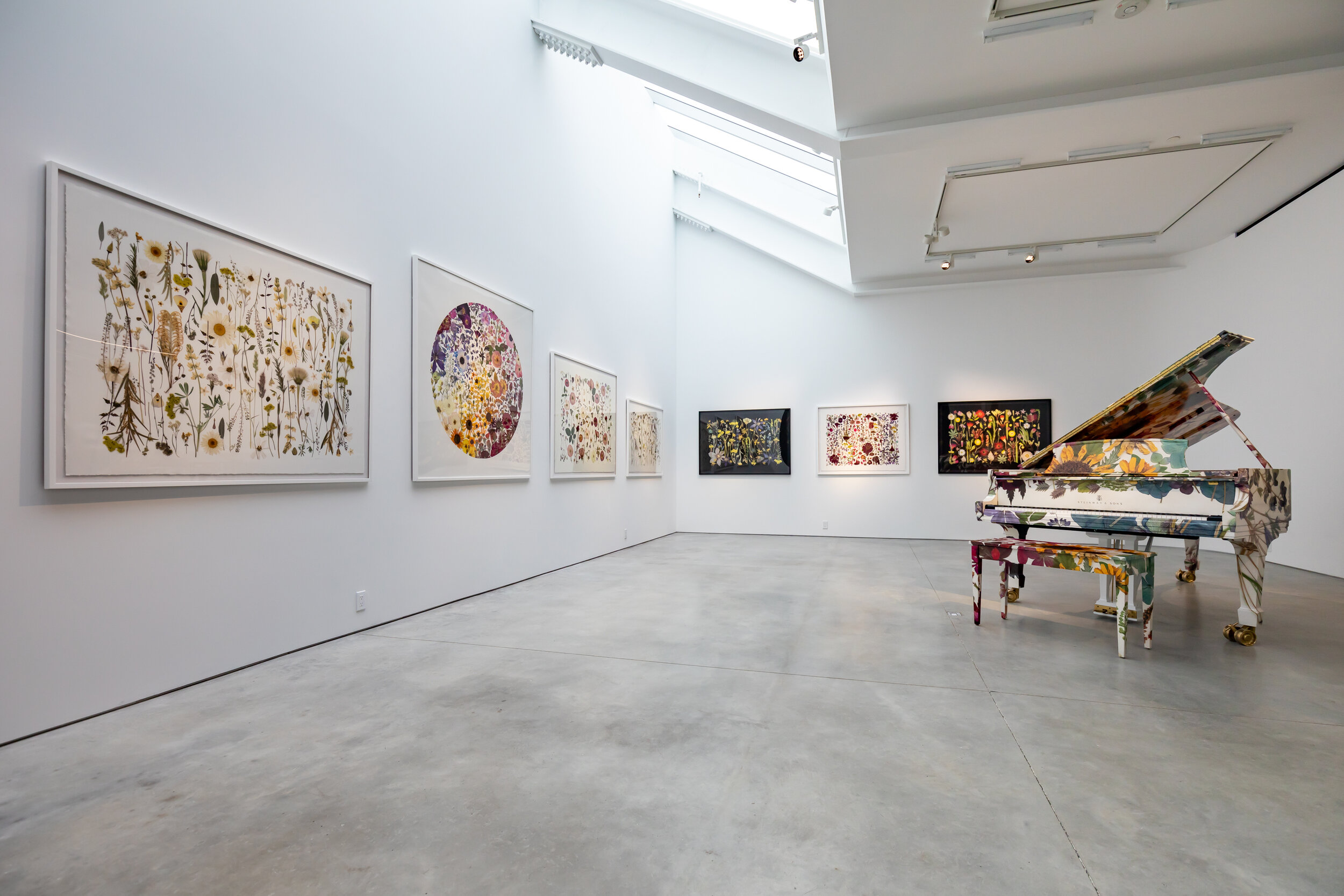Installation shot of large botanical floral prints and a botanical wrapped piano in a gallery