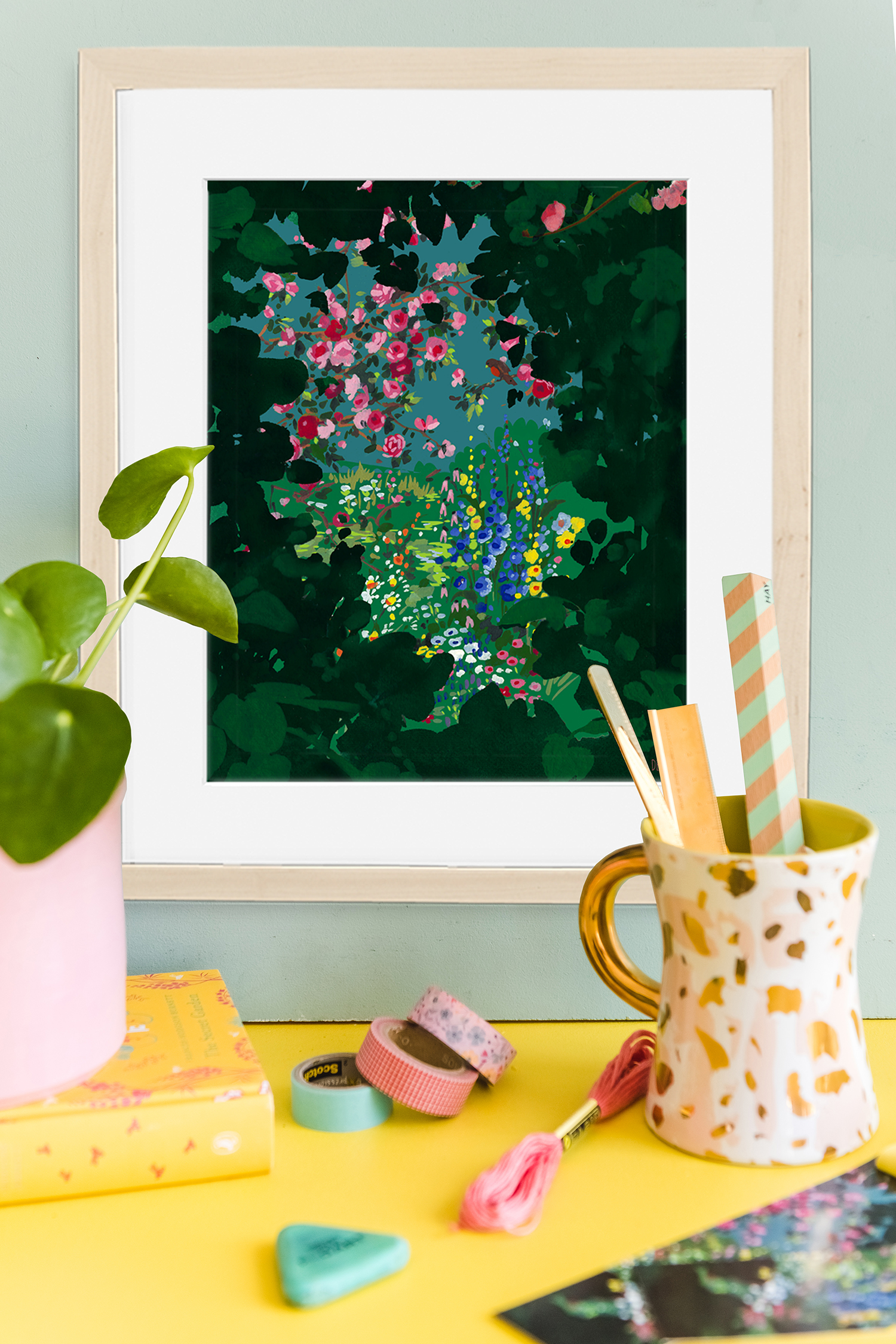 A print of flowers in a green secret garden tunnel hangs on the wall in front of a plant and some craft supplies