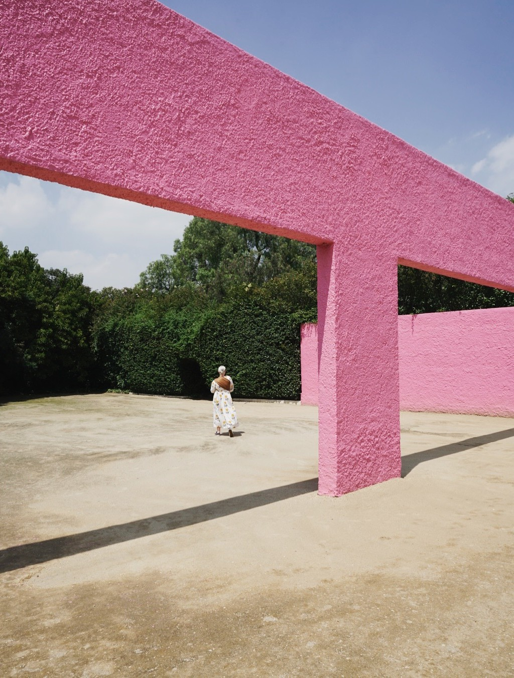 Brittany walks under a bright pink structure at Luis Barragán's San Cristobal stables in Mexico City