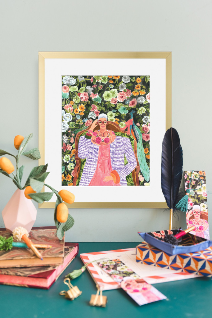 Iris Apfel print by Rosie Harbottle against a sage wall surrounded by stationary and paper plants.