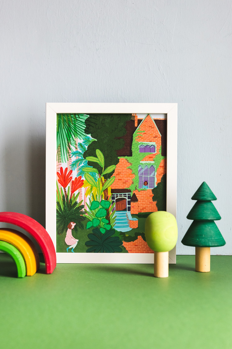 An art print of girls inside and outside a brick building covered with vines and surrounded by trees and flowers. Next to the print are wooden toys shaped like trees and a rainbow.
