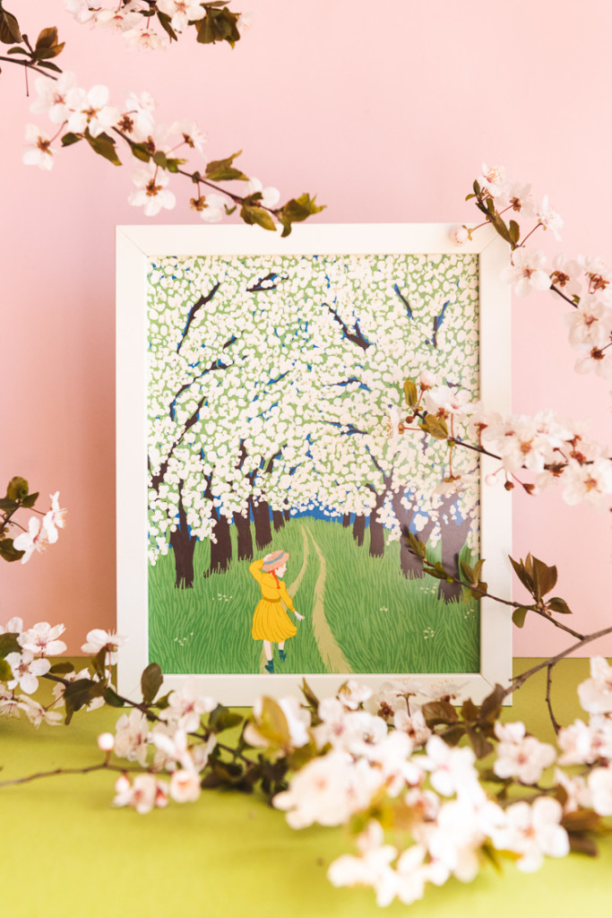 A print of Anne Shirley from Anne of Green Gables walking through a corridor of blossoms against a pink background with real blossoms in front.