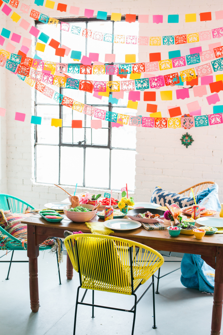 a festive Cinco de Mayo table set with Mexican food and decorated with colorful papel picado banners