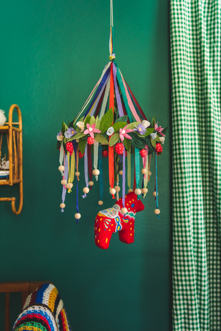 A colorful chandelier with a hanging Dala horse is i