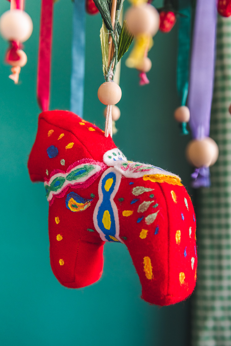 Close up of a colorful chandelier with a hanging Dala horse is i