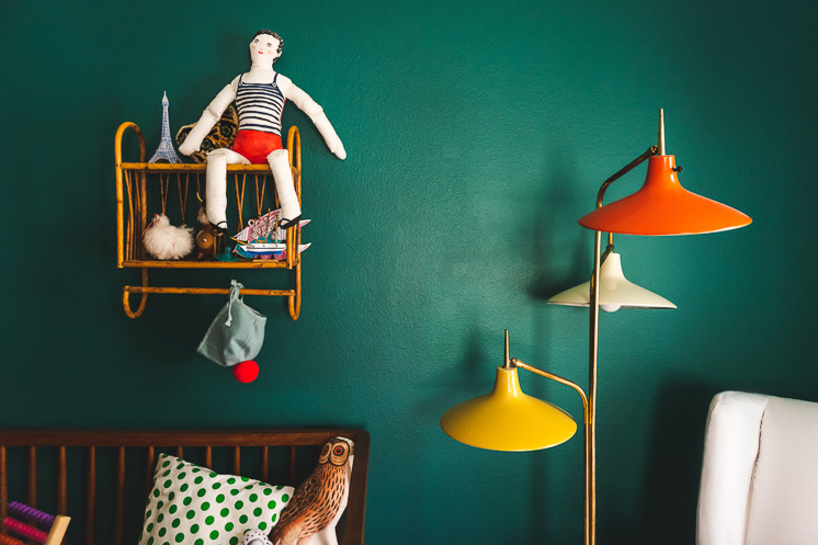 An interior shot featuring a painted green wall with a brightly colored lamp and a toy doll perched on a wicker shelf.