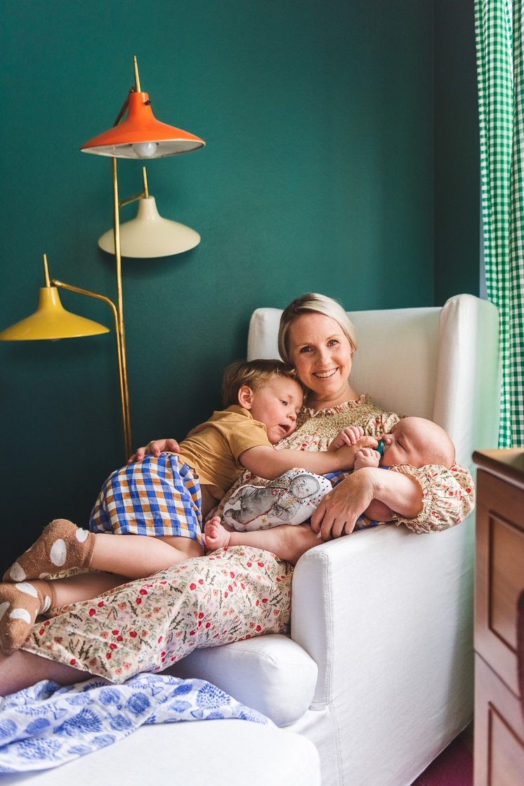 Brittany sits in a white rocking chair against a green wall and snuggles Jasper and Felix.