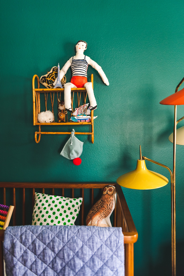Interior shot of a child's room with a green wall, a wicker shelf with a toy on it, and a crib. The crib has a denim-colored quilt hanging over the side.