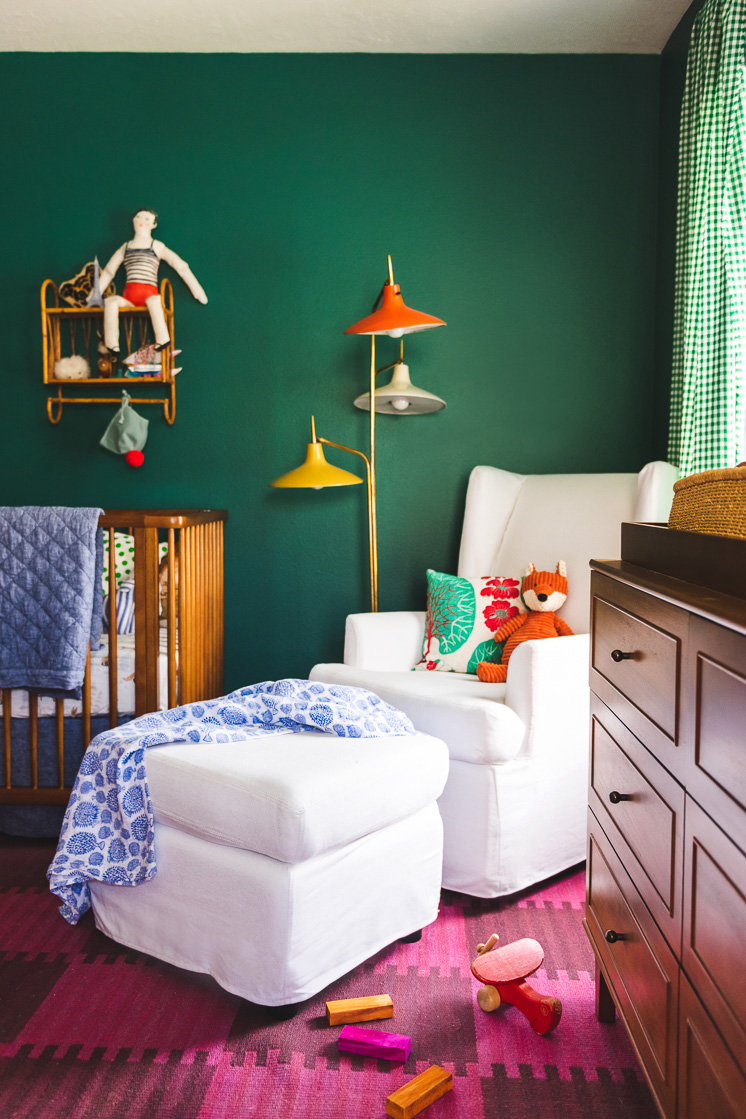 Interior shot of a child's room. Walls are green, A pink checkerboard rug is on the floor. A white rocking chair is central in the image.