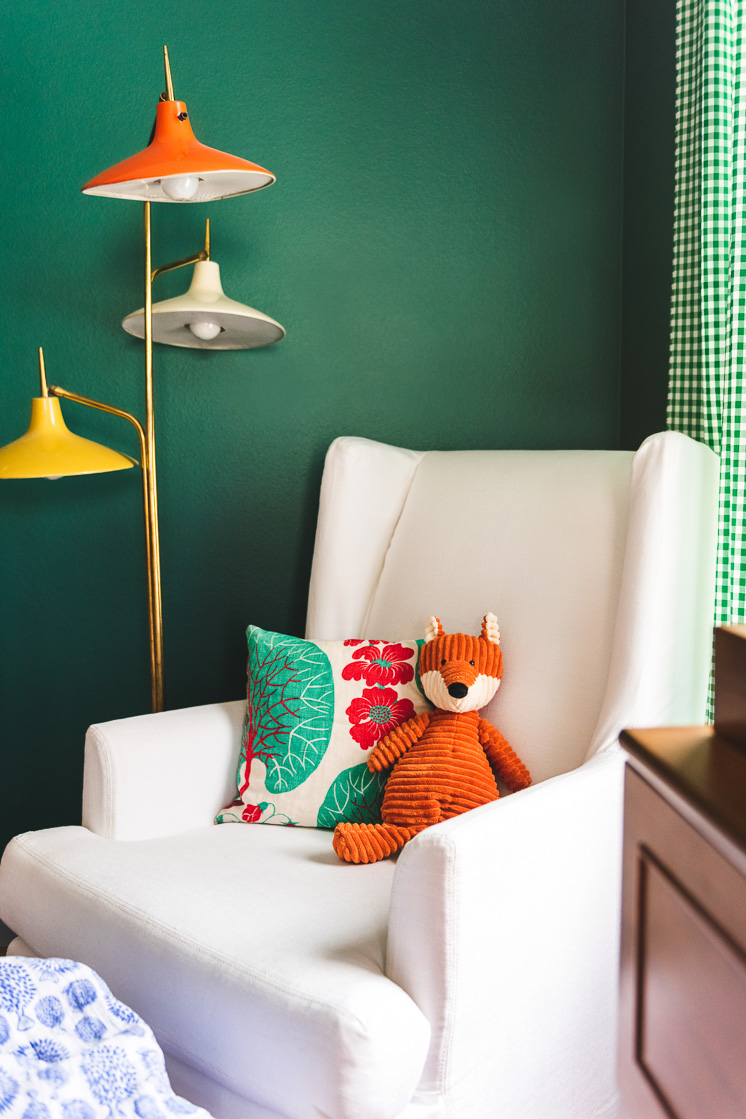 A white rocking chair against a green wall with a colorful lamp in the background. An orange stuffed fox and a pillow are on the chair.