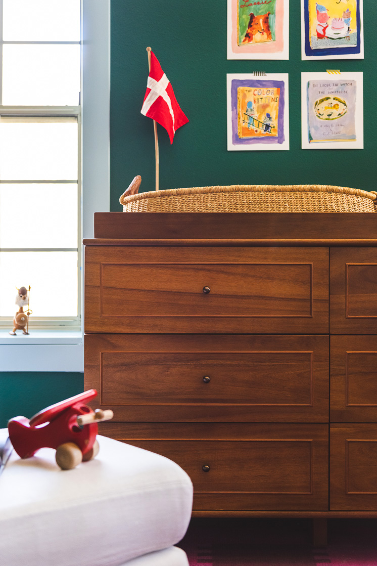 Interior shot of a nursery. In the foreground, a red toy airplane rests on a white ottoman. In the background is a wooden dresser with a small Danish flag on top and some illustrations on the wall.