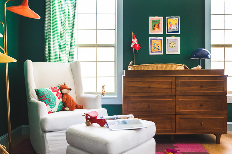 Interior shot of a green nursery. In the foreground is a white rocking chair with a few pillows, toys, and books on it and in the background is a wooden dresser.
