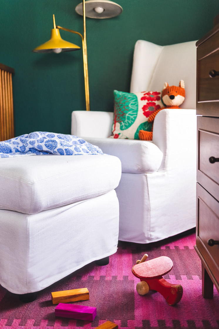 A white rocking chair against a green wall with a colorful lamp in the background. An orange stuffed fox and a pillow are on the chair. The floor is covered by a magenta checkerboard rug with a few wooden cars and an airplane on it.
