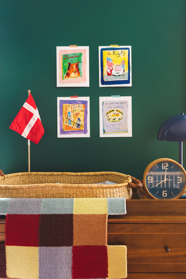A wooden dresser with a clock, changing basket, Danish flag, and blanket on top. The wall has a few illustrations hanging on it.