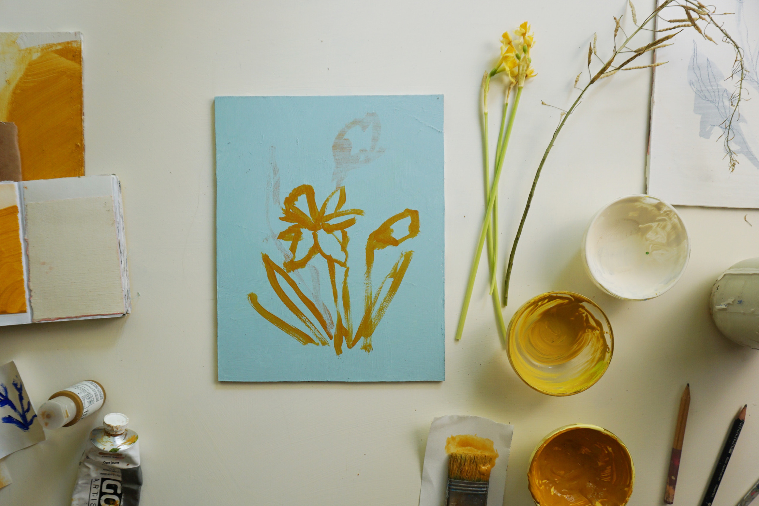 A styled shot of Rachel Smith's Daffodil I print in progress with paint pots and papers around it.